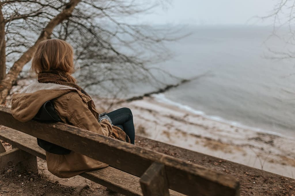 a woman sits on a bench overlooking a gloomy coastline