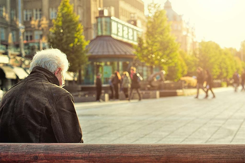 an elderly man sits on a bench in a city square, looking down
