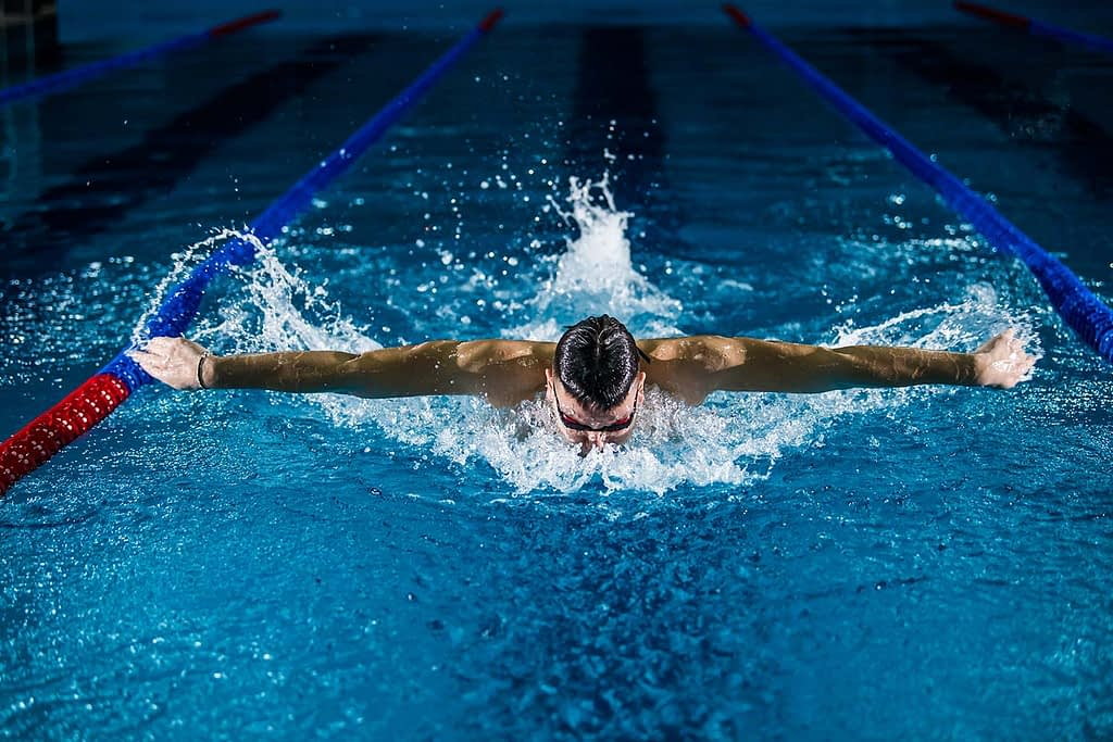 a male swimmer does a breaststroke in a swimming pool