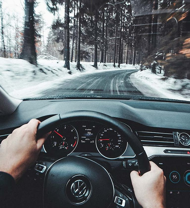 a steering wheel with two hands gripping it as the car drives on an icy road