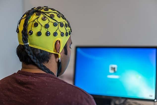 a man wearing a neurofeedback cap looks at a screen