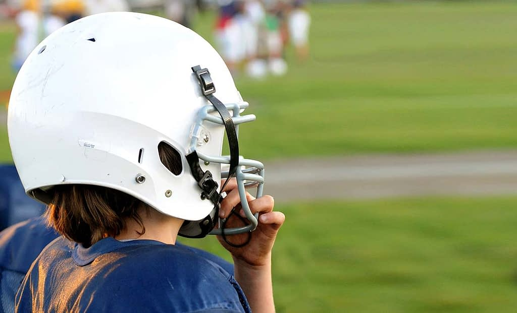 a child wearing a football helmet stands on the sidelines