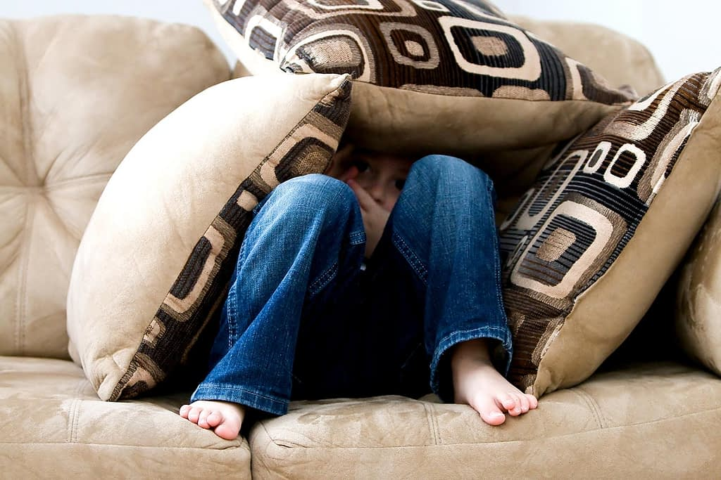 a young child hides under pillows while sitting on a couch