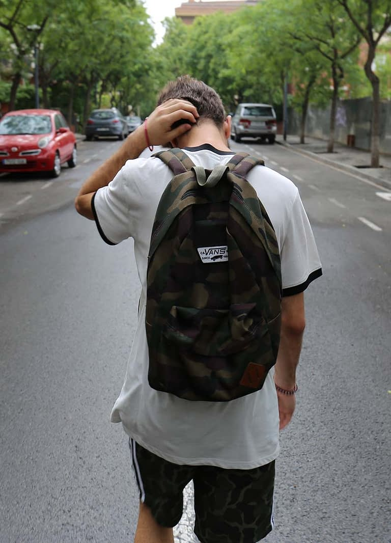 a teenage boy walks down a street wearing a backpack looking down