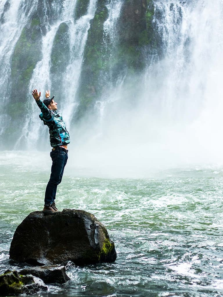 a young man stands on a rock in front of a waterfall raising his arms