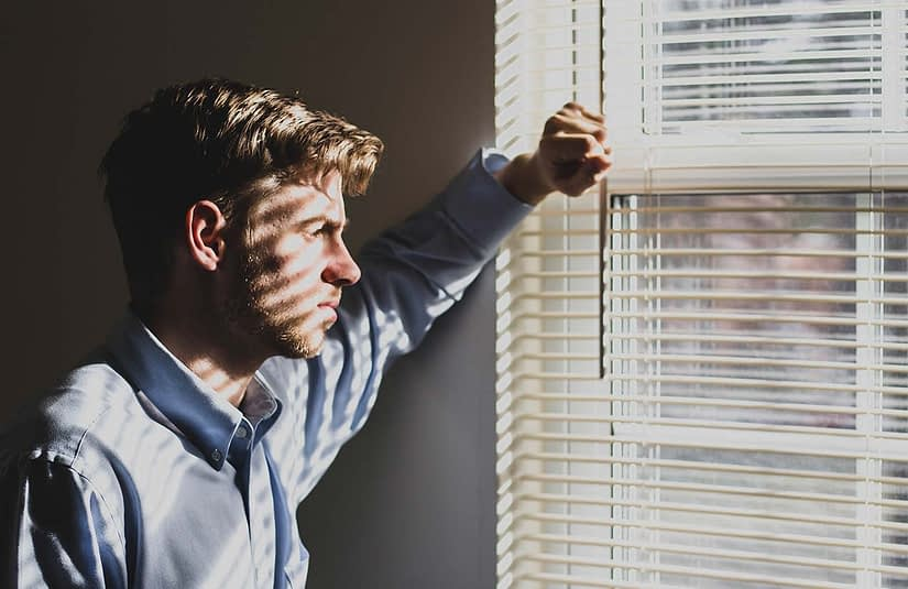 a young man looks out a window, he looks sad